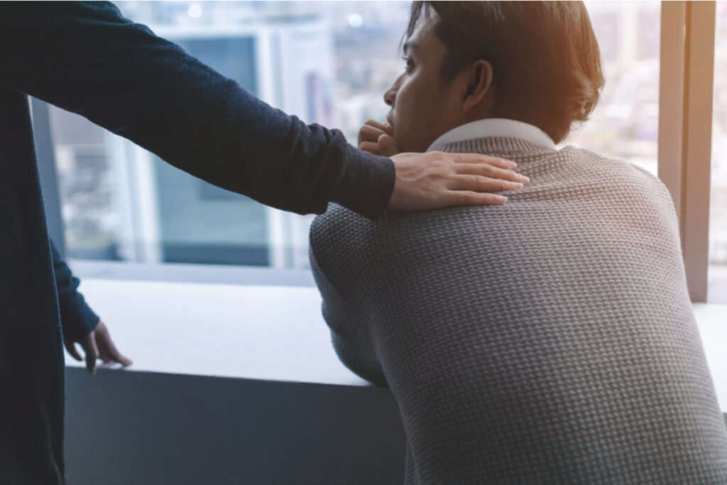 Person placing a comforting hand on an employee's shoulder